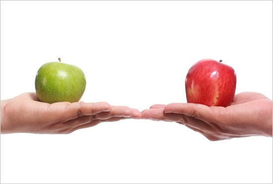 One hand holding green apple next to another hand holding red apple.